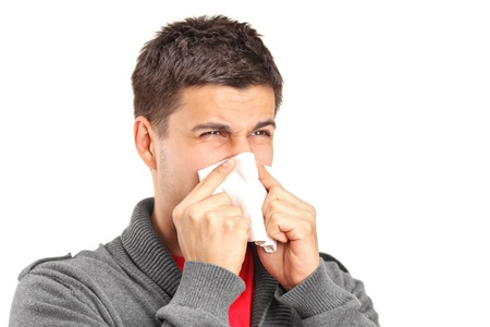 Infected man blowing his nose in tissue paper because of being ill isolated on white background photo