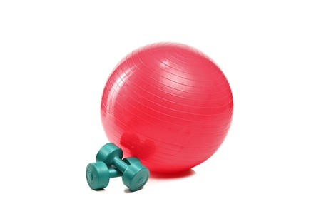A studio shot of a pilates ball and dumbbells isolated on white background photo