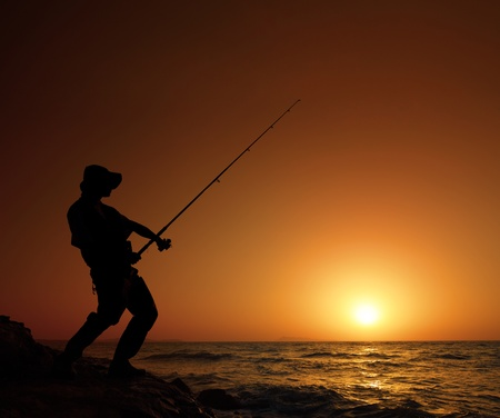 sportfishing: A young fisherman fishing with sunset in the background