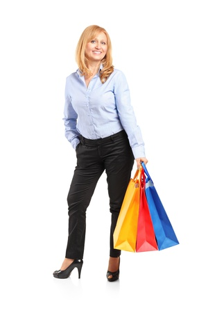 Full length portrait of a smiling female posing with shopping bags isolated on white background Stock Photo - 12633862