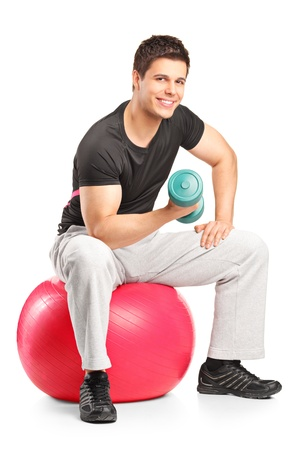 Smiling male lifting up a dumbbell seated on a fitness ball isolated on white background photo
