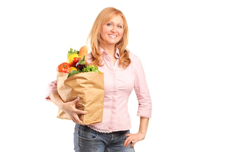 A smiling woman holding a paper bag full of groceries isolated on white background Stock Photo - 12633860