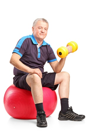 A mature man lifting up a dumbbell seated on a fitness ball isolated on white background photo