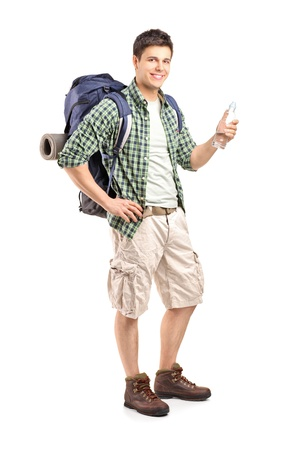 Full length portrait of a young hiker holding a bottle of water isolated on white background photo
