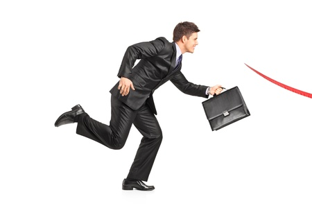 businessman running: Businessman with a briefcase running towards a finish line isolated on white background