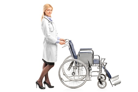 Full length portrait of a healthcare professional pushing a wheelchair isolated on white background photo