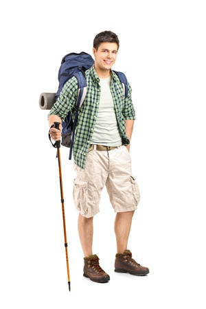 trekking pole: Full length portrait of a hiker with backpack and hiking poles posing isolated on white background