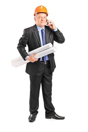 Full length portrait of a mature construction worker holding blueprints and talking on a phone isolated on white background  photo