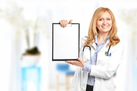 Portrait of a smiling healthcare professional holding a clipboard and posing in her office Stock Photo - 12633923