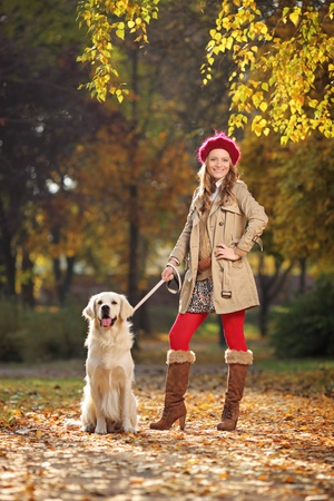 autumn in the city: Smiling young woman with her labrador retreiver dog in a city park Stock Photo