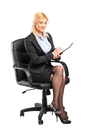 Young businesswoman sitting on a chair and writing on a clipboard isolated on white background Stock Photo - 12633905