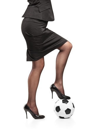 Woman in high heeled shoes standing on a soccer ball isolated on white background photo