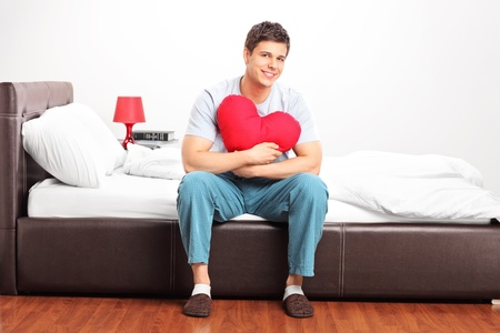 Young man sitting on a bed and holding a heart shaped pillow Stock Photo - 12633935