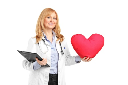 heart doctor: A mature healthcare professional holding a clipboard and red heart shape pillow isolated on white background