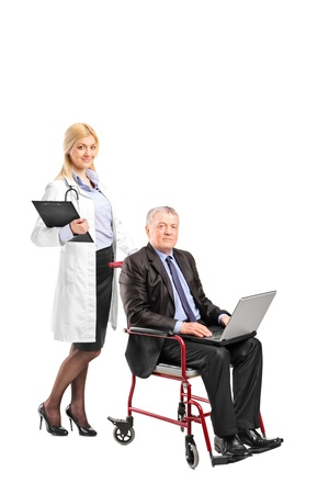 A nurse pushing a busy businessman working on a laptop in a wheelchair isolated on white background photo