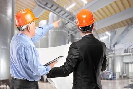 supervisores: Un equipo de trabajadores de la construcci�n con cascos anaranjados en el lugar de trabajo en una f�brica Foto de archivo