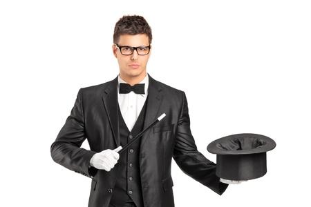 sombrero de mago: Un asistente de la celebraci�n de una varita m�gica y sombrero de copa vac�a sobre fondo blanco