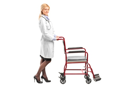 Full length portrait of a nurse pushing a wheelchair isolated against white background photo
