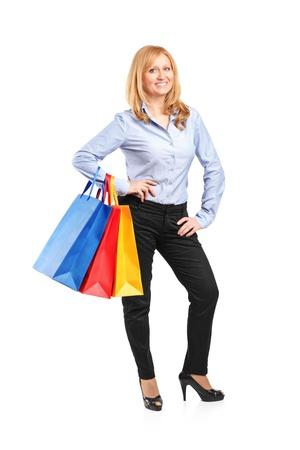 Full length portrait of a smiling woman posing with shopping bags isolated against white background Stock Photo - 12883181
