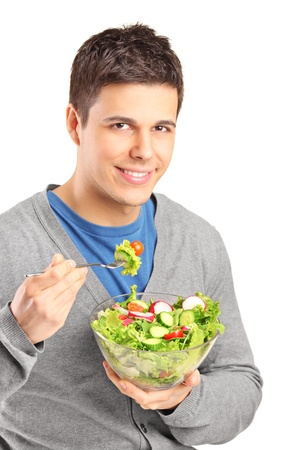 salad fork: A young man eating salad isolated on white background