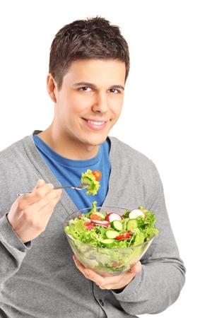 hombre comiendo: Un hombre joven que come la ensalada aislada en el fondo blanco Foto de archivo