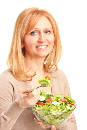 A young woman eating salad isolated on white background photo