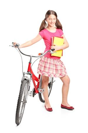 niños en bicicleta: Retrato de cuerpo entero de una niña sosteniendo un portátil y una bicicleta aislado sobre fondo blanco