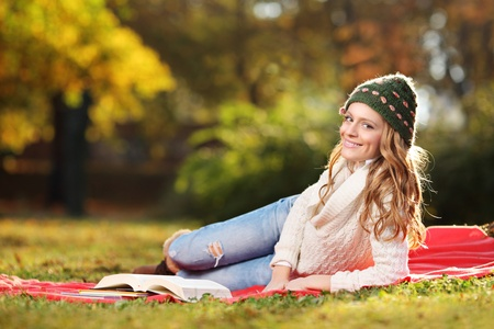 Young woman reading a book in the city park