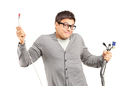 cable tangle: A confused male holding electronic cables isolated on white background
