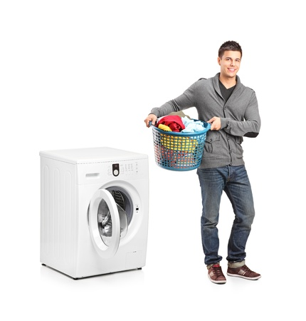 laundering: Full length portrait of a man with laundry basket posing next to a washing machine isolated on white background