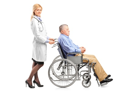 Full length portrait of a nurse or doctor pushing a handicapped senior man in a wheelchair isolated on white background photo