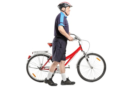 Full length portrait of a senior bicyclist pushing a bicycle isolated on white background Stock Photo - 12883296