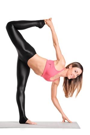 Retrato de cuerpo entero de una atractiva instructora de pilates haciendo ejercicio aislado sobre fondo blanco Foto de archivo