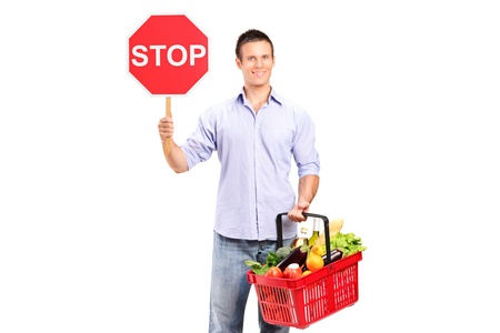 Stop and shop here A male holding a full shopping basket and a stop road sign isolated on white background photo