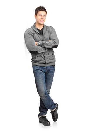 Full length portrait of a happy young man leaning against wall isolated on white background