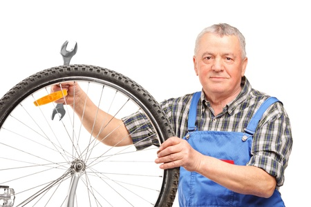 Middle aged man holding wrench and repairing bicycle wheel isolated over white background photo