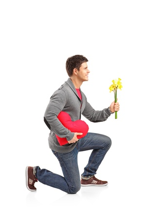 kneeling man: A young man holding a heart shaped pillow and bunch of flowers isolated on white background
