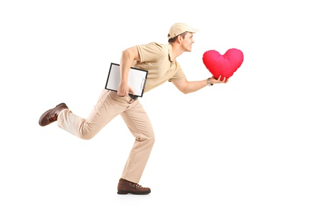 Delivery boy in a rush delivering red heart shaped pillow isolated on white background photo
