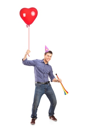 Full length portrait of a happy male holding a balloon and a horn isolated on white background Stock Photo - 13008216