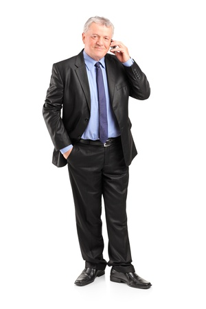 Full length portrait of a mature businessman talking on a phone isolated on white background photo