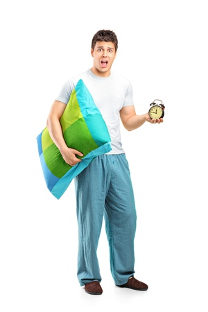 Full length portrait of a shocked male holding a pillow and alarm clock isolated on white background Stock Photo - 13008166