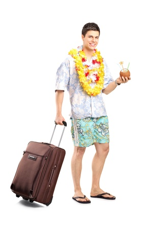 Full length portrait of a smiling man with cocktail carrying his luggage isolated on white background photo