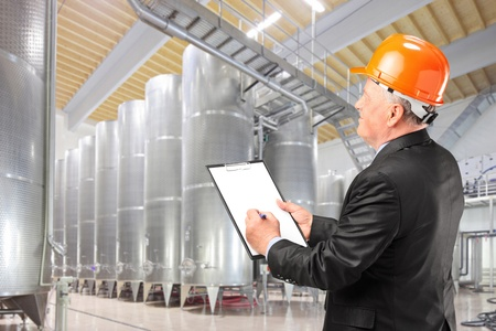 engineering clipboard: A construction worker with orange helmet at work place  Stock Photo