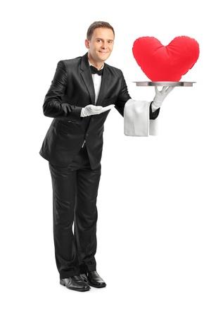 sirvientes: Retrato de cuerpo entero de un mayordomo que sostiene una bandeja con forma de corazón rojo en él aislados sobre fondo blanco Foto de archivo