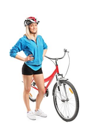 ciclista: Retrato de cuerpo entero de una mujer motorista con casco posando junto a una bicicleta sobre fondo blanco Foto de archivo