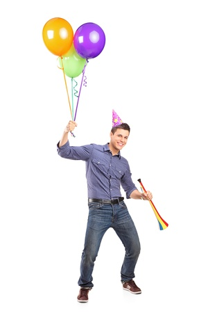 euphoric: Full length portrait of a happy male holding balloons and a horn isolated on white background