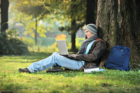 laptop outside: A man working on a laptop in the city park