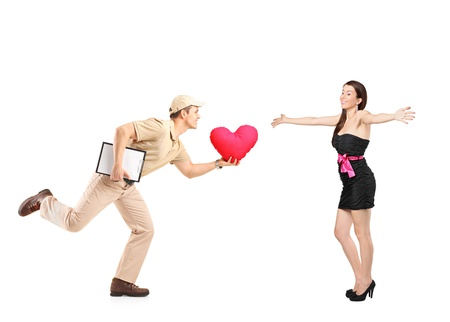 Delivery boy in a rush delivering red heart shaped pillow and excited woman isolated on white background photo