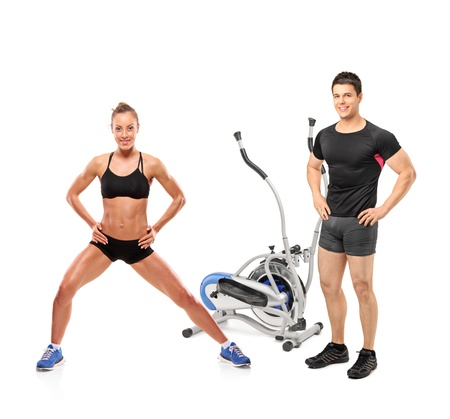 fitness equipment: Full length portrait of female and male athletes posing next to a cross trainer machine isolated on white background Stock Photo