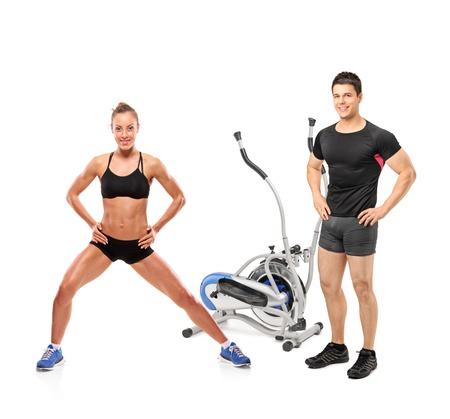 ejercicio aer�bico: Retrato de cuerpo entero de los deportistas hombres y mujeres posando junto a una m�quina el�ptica aislada sobre fondo blanco